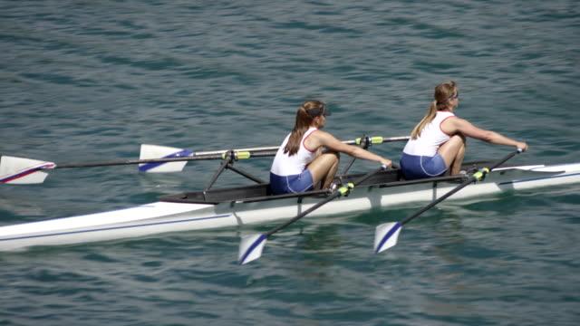vídeos de stock, filmes e b-roll de atletas do sexo feminino lemada um lago ensolarado em um double scull - remo esporte aquático