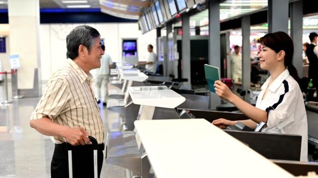Female attendant giving boarding pass to passenger