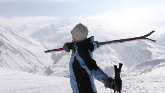 Female backcountry skier ascends snow slope above mountains High mountain snow slope, valley below, Livigno, Lombardy lombardy stock videos & royalty-free footage