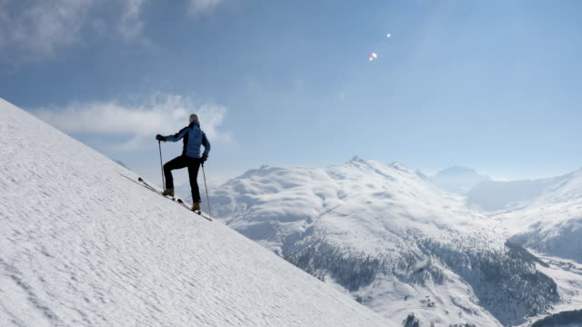 female backcountry skier ascends snow slope above mountains - livigno video stock e b–roll