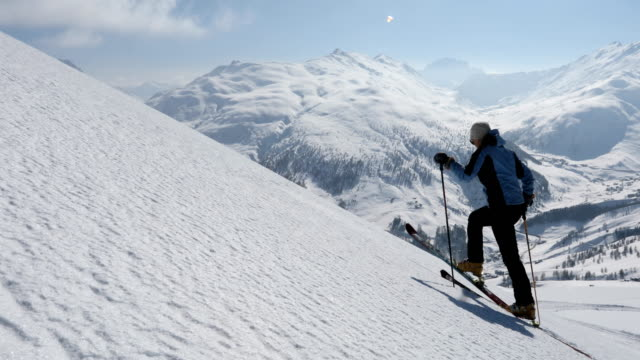 female backcountry skier ascends snow slope above mountains - lombardia video stock e b–roll