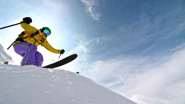 slo mo female backcountry skier jumping off a rock - sci freestyle video stock e b–roll