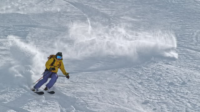 slo mo female backcountry skiing riding down the mountain - sci freestyle video stock e b–roll