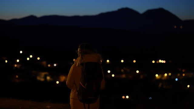 Female backpacker enjoying the windy adventure on the edge of a hill, while admiring the view of a sleepy city