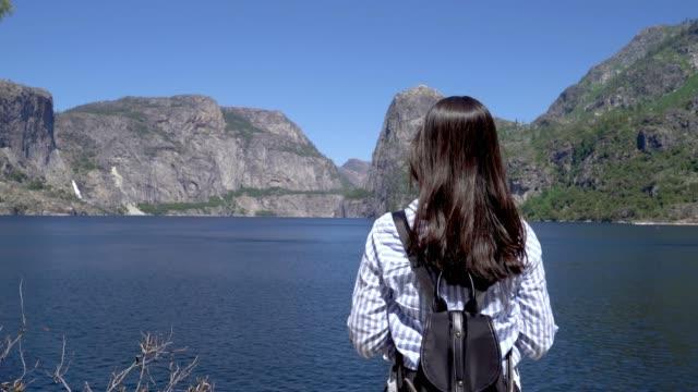 山に囲む女性バックパッカー - 川岸点の映像素材/bロール
