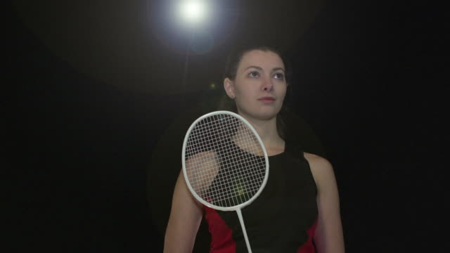 Female Badminton Player Portrait pose - Super Slow Motion 180 degree rotation Stock HD video clip footage of a female Badminton Player. Filmed in Super Slow motion, the camera rotates 180 degrees around the player. Black Background. Indoors pre game stock videos & royalty-free footage
