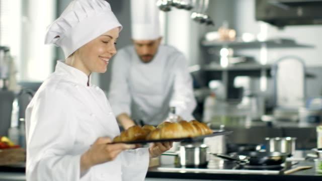 female baker carries tray with freshly baked croissants. - taca filmów i materiałów b-roll