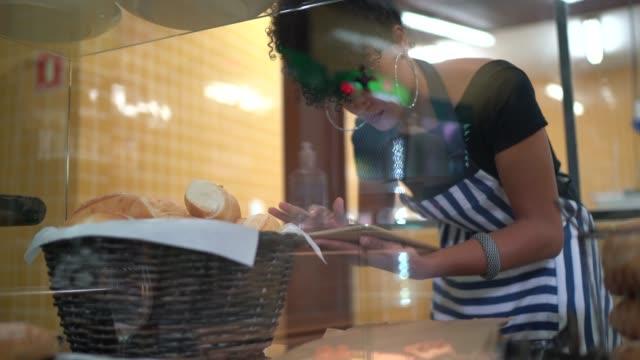 stockvideo's en b-roll-footage met vrouwelijke bakker het controleren van brood in de bakkerij - bakery
