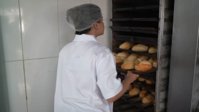 Female baker taking fresh bread out of the oven