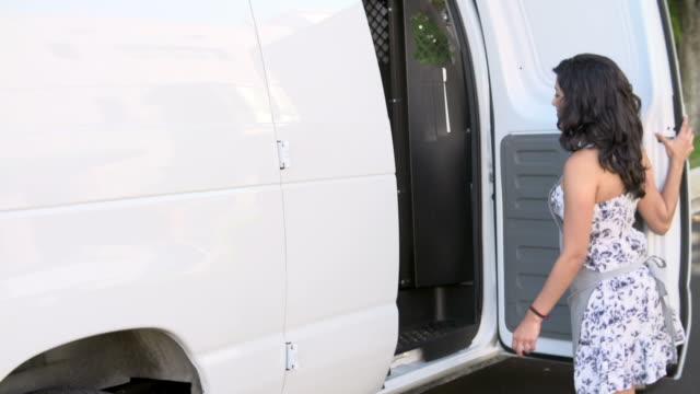 female baker unloading bread from van in slow motion - gıda ve i̇çecek sanayi stok videoları ve detay görüntü çekimi