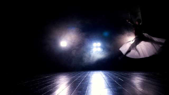 A female ballet dancer jumps across a dark stage. video