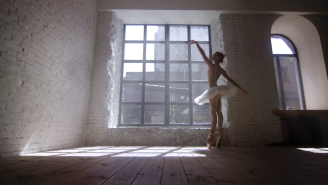 female ballet dancer training in loft style studio in front of big window - baletnica filmów i materiałów b-roll