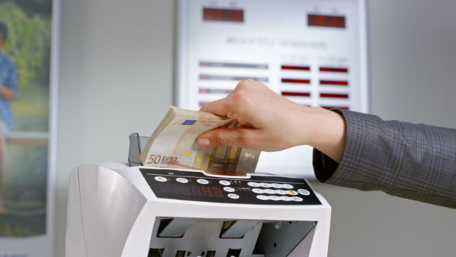 Female bank employee inserting  fifty euro banknotes into the automated currency counter Medium handheld shot of a female bank clerk inserting fifty euro banknotes into the money counter. Shot in Slovenia. bank counter stock videos & royalty-free footage