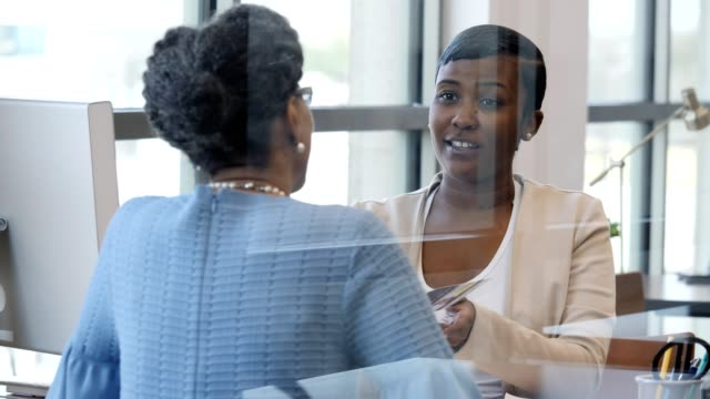 Female bank employee reviews bank informational flyer with customer