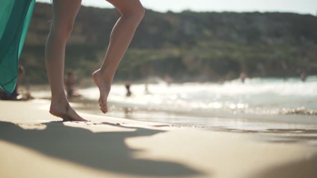 Female bare feet walking on the wet sand on the beach. Female legs posing in the sun at a seaside resort.