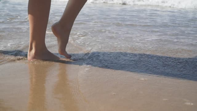 Female bare feet walking on the wet sand on the beach. Slow motion
