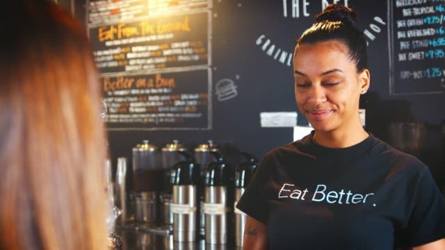 kadın barista müşteri paket servisi olan restoran kahve ile hizmet veren cafe - sipariş vermek stok videoları ve detay görüntü çekimi