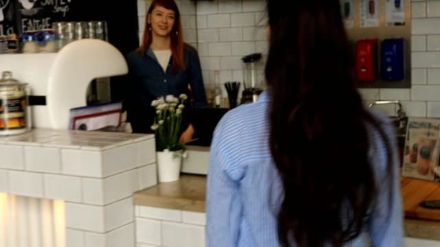 female barista taking order from customer at cafe - entrata video stock e b–roll