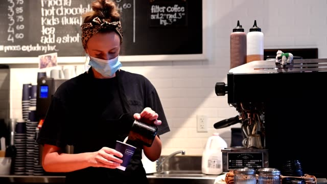 Female barista wearing a protective face mask Woman wearing a protective face mask for COVID-19 safety. Female barista making pastries. Reopening the economy after the coronavirus. wait staff stock videos & royalty-free footage