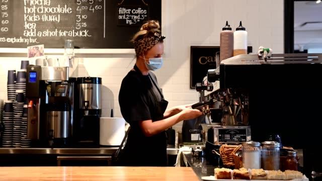 weibliche barista trägt eine schützende gesichtsmaske - barista stock-videos und b-roll-filmmaterial