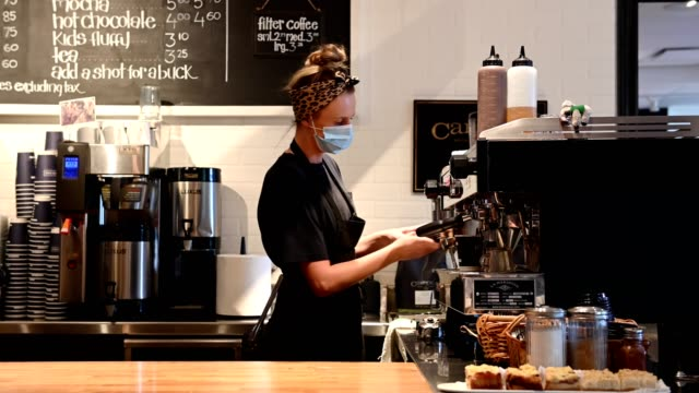 female barista wearing a protective face mask - caffetteria video stock e b–roll