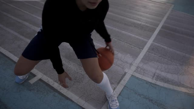 Female basketball player in morning light on professional court running with ball. Handhelded footage. Close up video