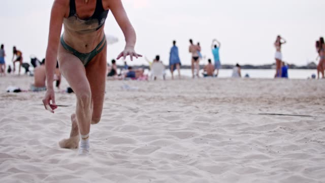 Female Beach Volleyball player diving on the sand during a game Female Beach Volleyball player diving on the sand during a game beach volleyball stock videos & royalty-free footage