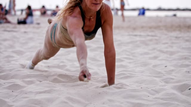 Female Beach Volleyball player diving on the sand during a game Female Beach Volleyball player diving on the sand during a game volleyball ball stock videos & royalty-free footage
