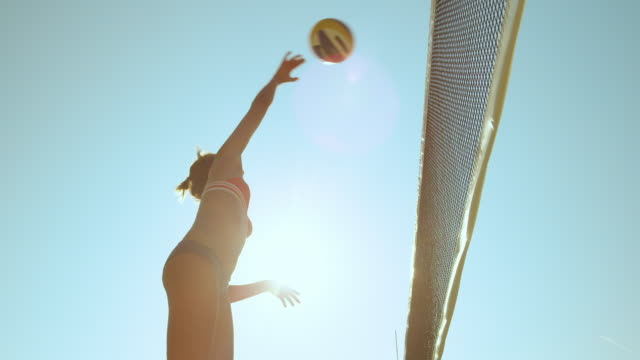 LENS FLARE: Female beach volleyball player spikes the ball and scores a point. SLOW MOTION, LOW ANGLE, CLOSE UP, LENS FLARE: Athletic female beach volleyball player spikes the ball and scores a point during a competition. Cheerful girl enjoying the summer and playing voleyball. beach volleyball stock videos & royalty-free footage