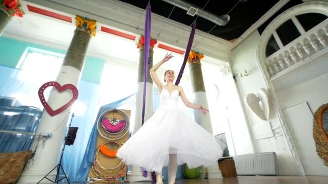 vídeos de stock e filmes b-roll de female beautiful ballerina in white tutu performs pirouette in spacious and modern studio - tule têxtil