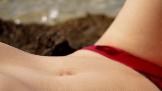 female belly sunbathing on the beach video