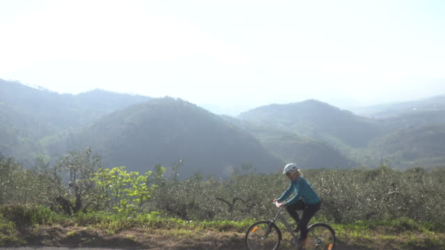 Female bicyclist pedals above sea, hills  pedal pushers stock videos & royalty-free footage