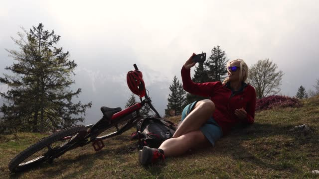 Female biker relaxes in alpine meadow, takes smart phone pic