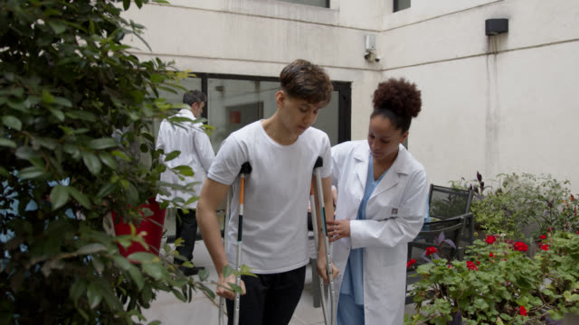Female black therapist helping teenage male patient while he walks with crutches at the patio of physical rehab clinic Female black therapist helping teenage male patient while he walks with crutches at the patio of physical rehab clinic - Incidental doctors at background orthopedic equipment stock videos & royalty-free footage