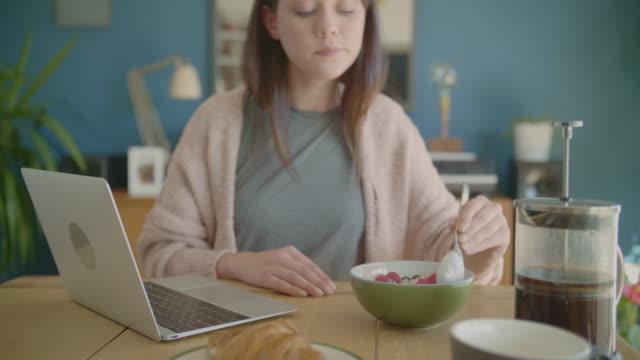 vídeos y material grabado en eventos de stock de mujeres blogger desayunando y el uso de laptop en la mesa - arándano