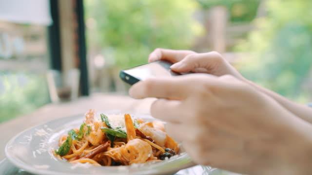 vidéos et rushes de blogger femelle photographier le déjeuner au restaurant avec son téléphone. photo jeune femme prise de nourriture de spaghetti sur smartphone, photographier les repas avec caméra mobile. - vaisselle picto
