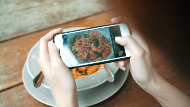 Female blogger photographing lunch in restaurant with her phone. A young woman taking photo of spaghetti food on smartphone, photographing meal with mobile camera. Female blogger photographing lunch in restaurant with her phone. A young woman taking photo of spaghetti food on smartphone, photographing meal with mobile camera. spaghetti stock videos & royalty-free footage