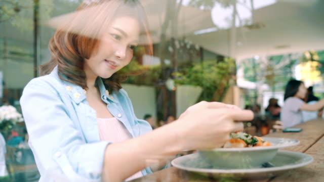 vídeos de stock, filmes e b-roll de blogger feminino fotografando o almoço no restaurante com o seu telefone. uma foto de jovem mulher tomada do alimento de espaguete no smartphone, fotografar a refeição com câmera móvel. - blogar
