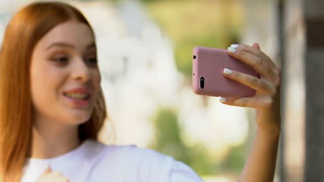 Female blogger shooting video smartphone application, creative job, technology