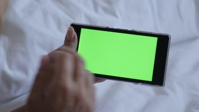 女性の金髪リラックス自宅と緑色の画面携帯電話を保持 - スマホ ベッド点の映像素材/bロール