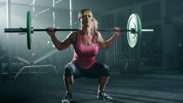 vídeos y material grabado en eventos de stock de mujer culturista haciendo ejercicio con pesas en gimnasio - entrenamiento con pesas