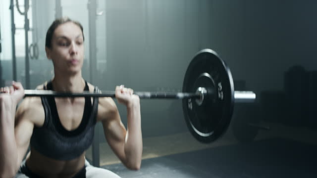 Female bodybuilder doing exercise with weights in gym video