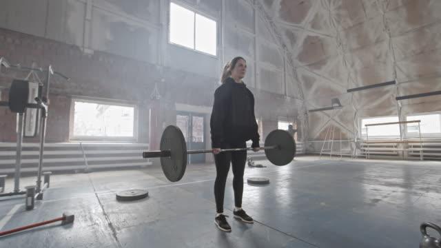 vídeos de stock e filmes b-roll de female bodybuilder having barbell workout - agachar se