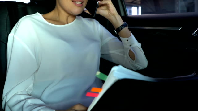 Female boss discussing weekly report with colleague on smartphone sitting in car