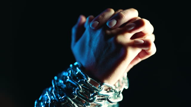 vidéos et rushes de mains liées femelles de l'esclave enchaînéavec la chaîne de fer sur le fond noir. esclavage, prisonnier, concept de violence. - ligoté