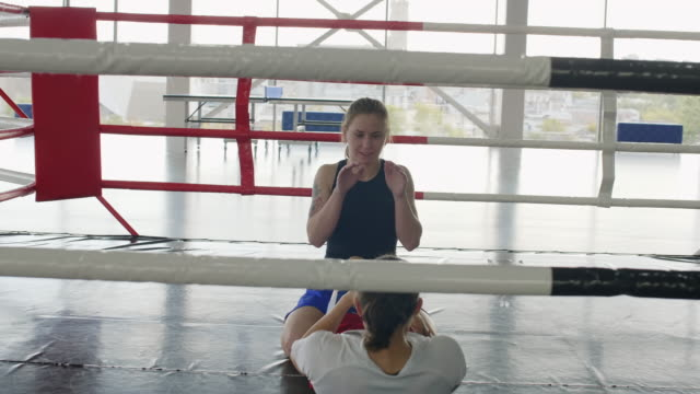 Female Boxer Doing Punching Sit Ups with Assistance of Partner on Ring