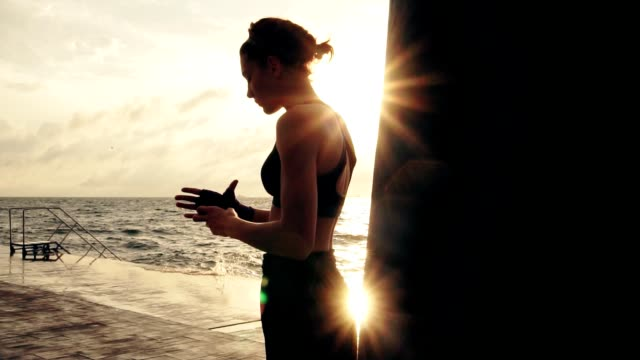 Female boxer getting her fists ready for the boxing gloves by wrapping bandage around them standing against the sun. Young woman wrapping hands with boxing wraps on the beach. Lens flare video