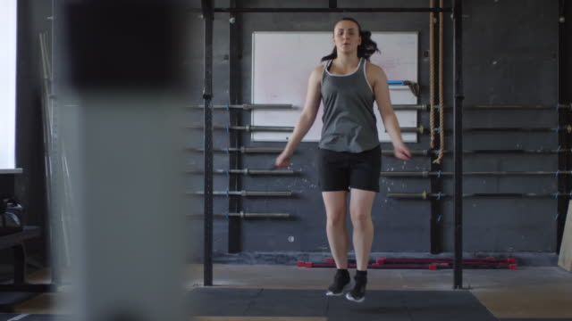Female Boxer Having Jump Rope Workout in Gym