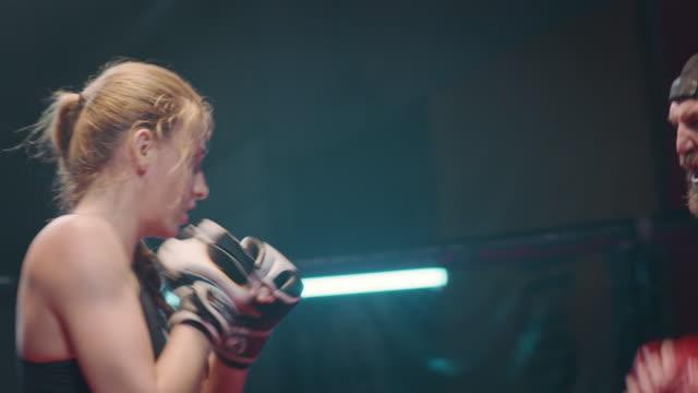 vídeos de stock, filmes e b-roll de sessão de trabalho boxer feminino com treinador - artes marciais
