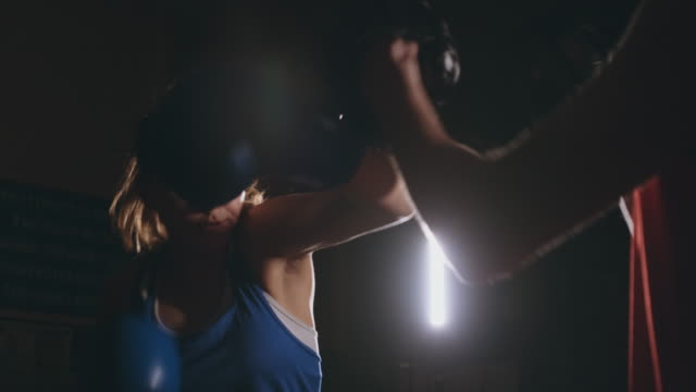 female boxer punching a focus mitts with boxing gloves in a smoky gym - sacco per il pugilato video stock e b–roll